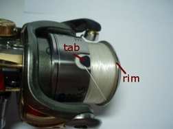 line holding tab on fishing reel